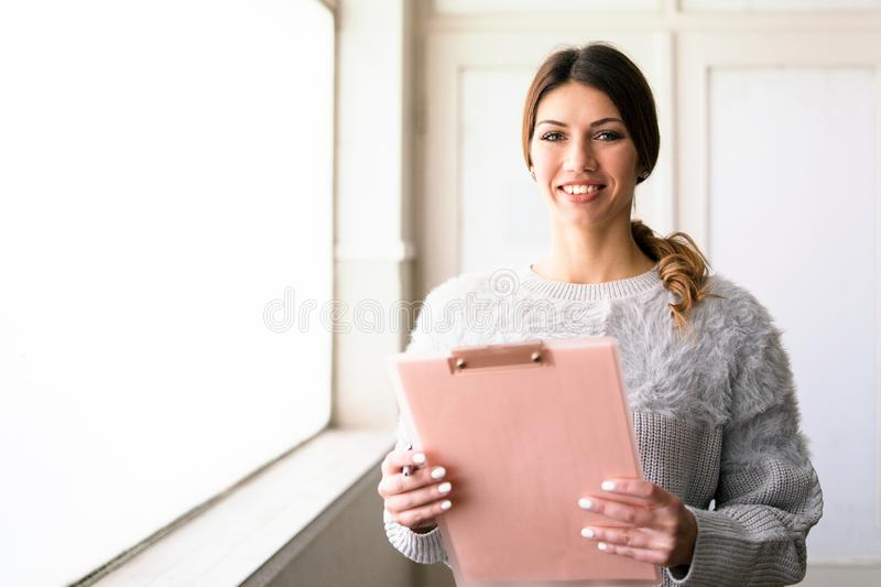 Young Woman Holding Clipboard by the Window At Work. Pretty Woman Smiling, standing by the window in the office. Secretary, holding clipboard, checking data and royalty free stock images
