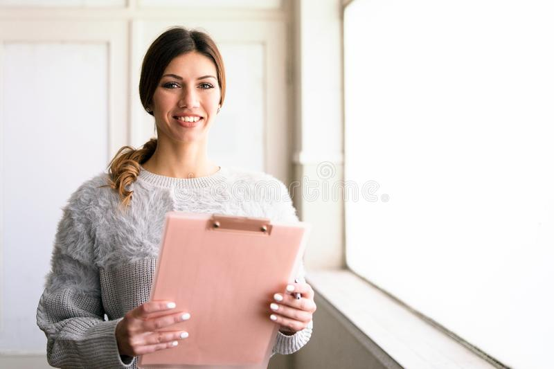 Young Woman Holding Clipboard by the Window At Work. Pretty Woman Smiling, standing by the window in the office. Secretary, holding clipboard, checking data and stock images