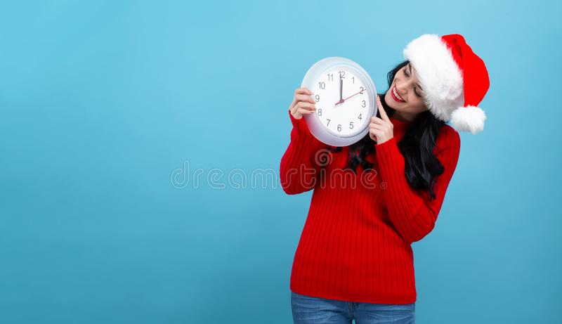 Young woman holding a clock showing nearly 12 stock photography