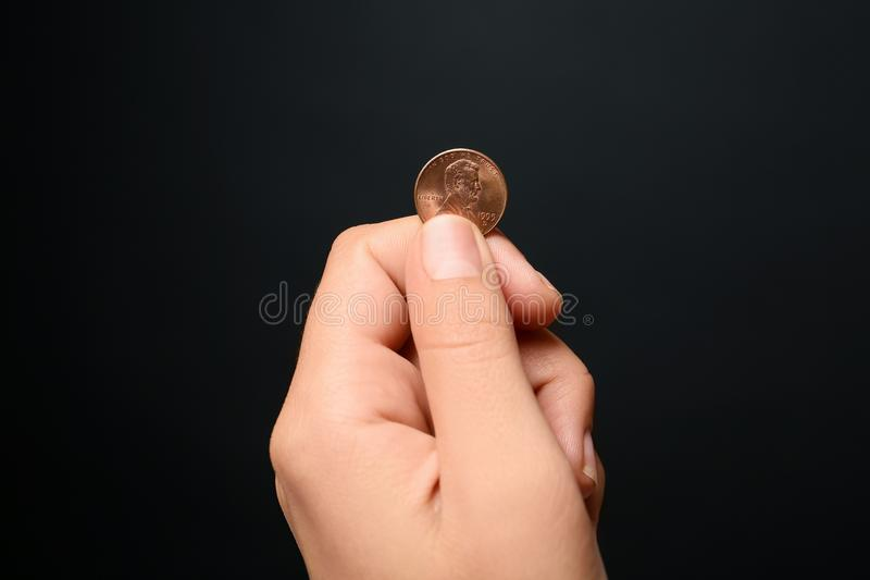 Young woman holding coin on black background. Closeup view stock photography