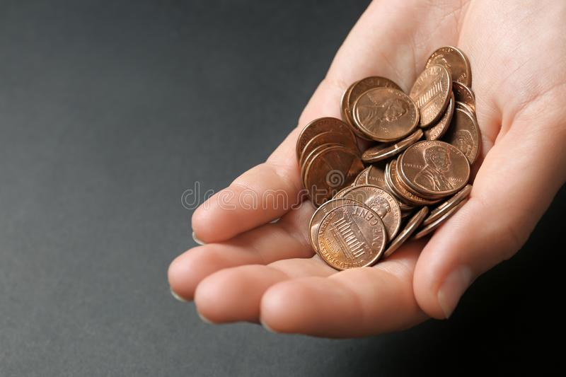 Young woman holding coins on black background. Closeup view royalty free stock photo