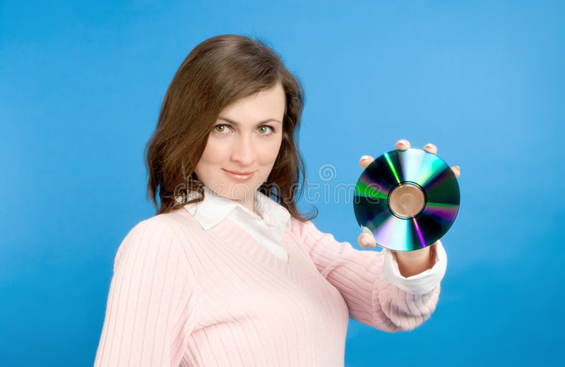 Young Woman Holding Compact Disc. Over blue background royalty free stock photos