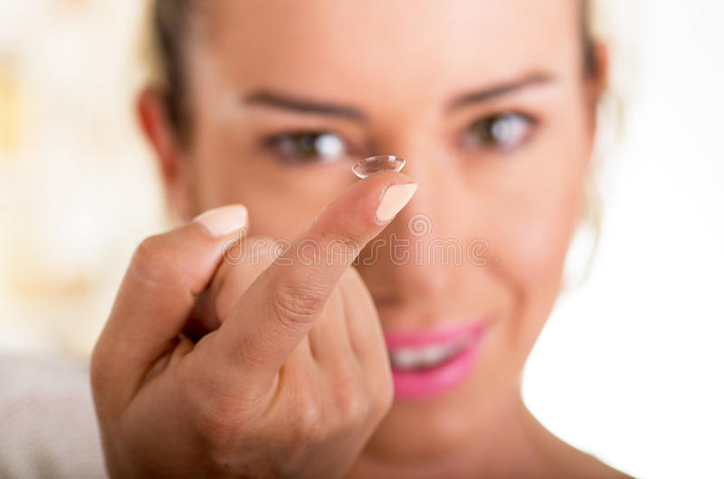 Young woman holding contact lens on finger in front of her face on white background., eyesight and eyecare concept.  stock image