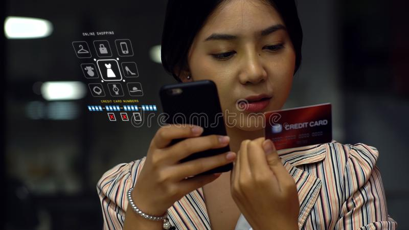 Young woman holding credit card and phone. Teenage girl making purchase over the phone and dictating the credit card details or texting the details, dark royalty free stock photos
