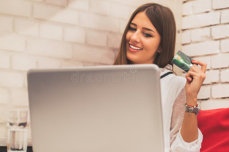 Young woman holding credit card and using laptop computer royalty free stock images
