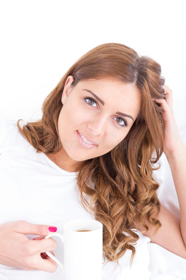 Young woman holding cup of coffee lying thinking r. Beautiful young woman holding cup of coffee lying thinking relaxing on the couch, sofa home indoors, happy royalty free stock photography