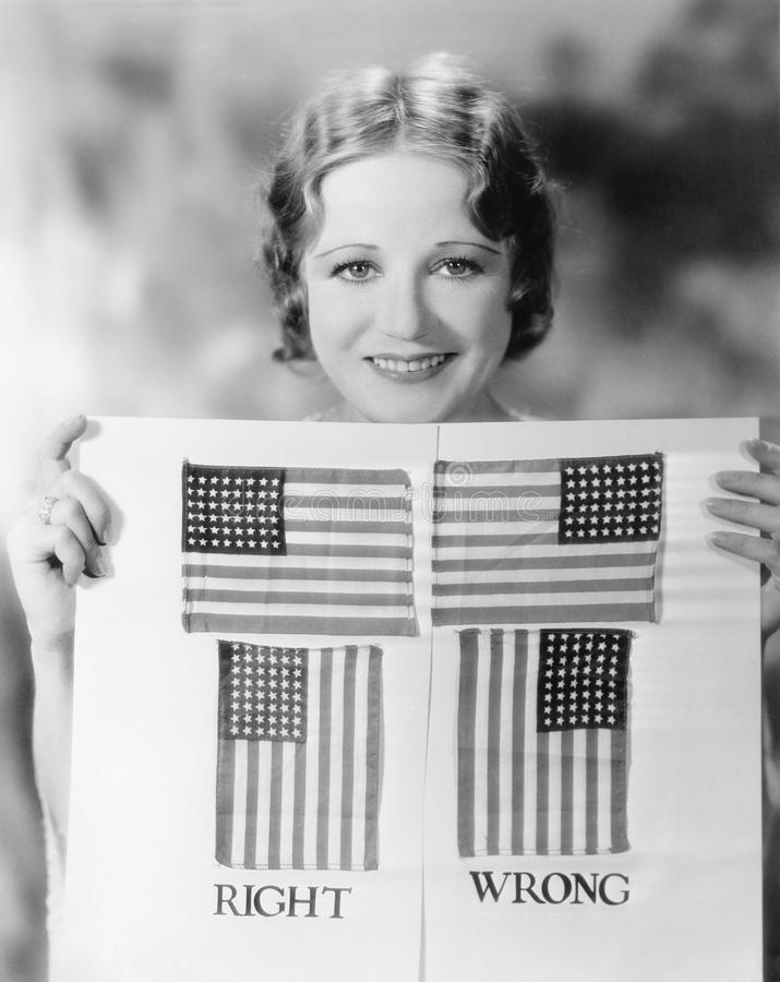 Young woman holding a diagram of how to hang an American Flag. (All persons depicted are no longer living and no estate exists. Supplier grants that there will stock image