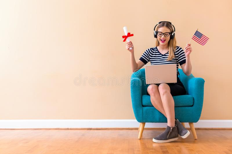 Young woman holding a diploma and USA flag with her laptop stock photography