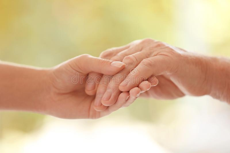 Young woman holding elderly man hand on blurred background, closeup royalty free stock photos