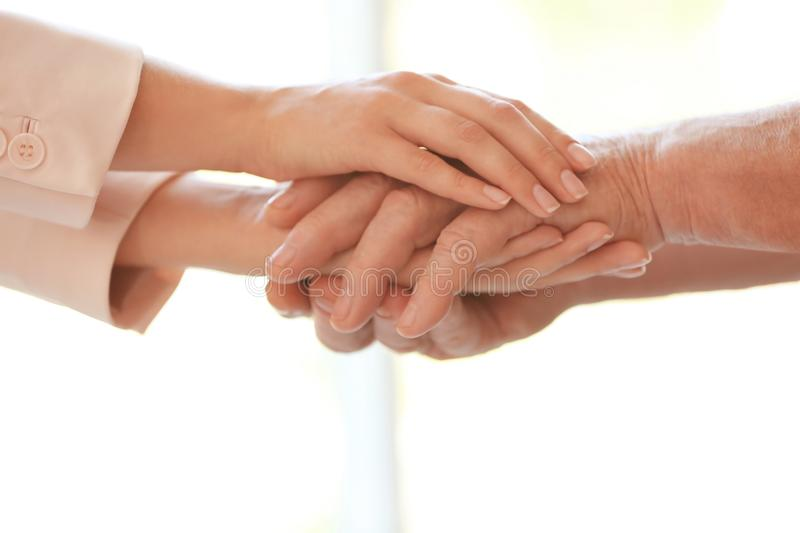 Young woman holding elderly man hands on blurred background, closeup. Help service stock photos