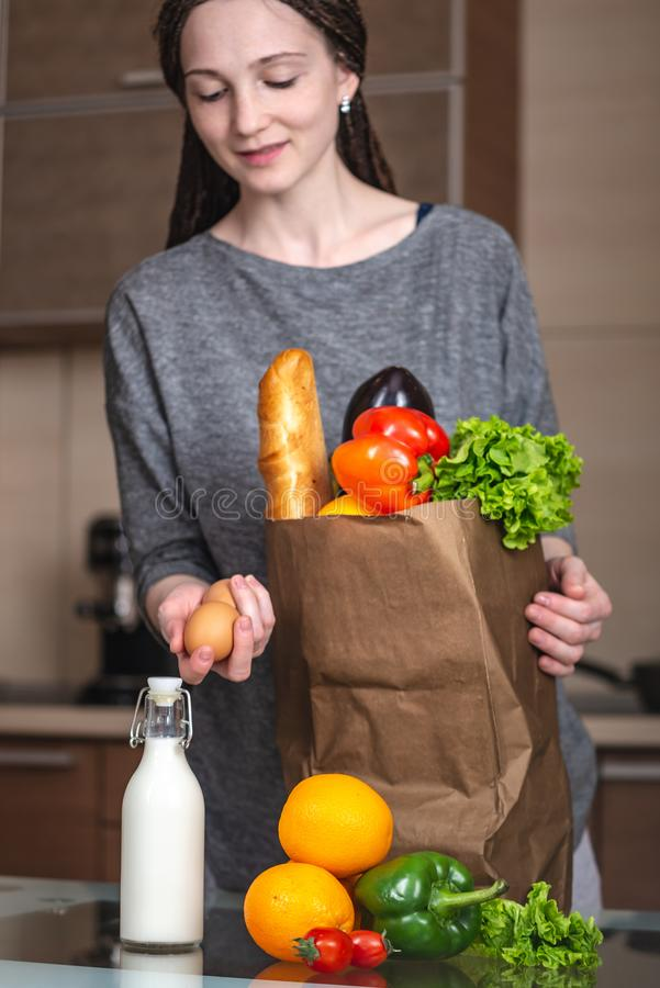Young woman holding full paper bag with products in hands on the background of the kitchen. Fresh organic food royalty free stock photo