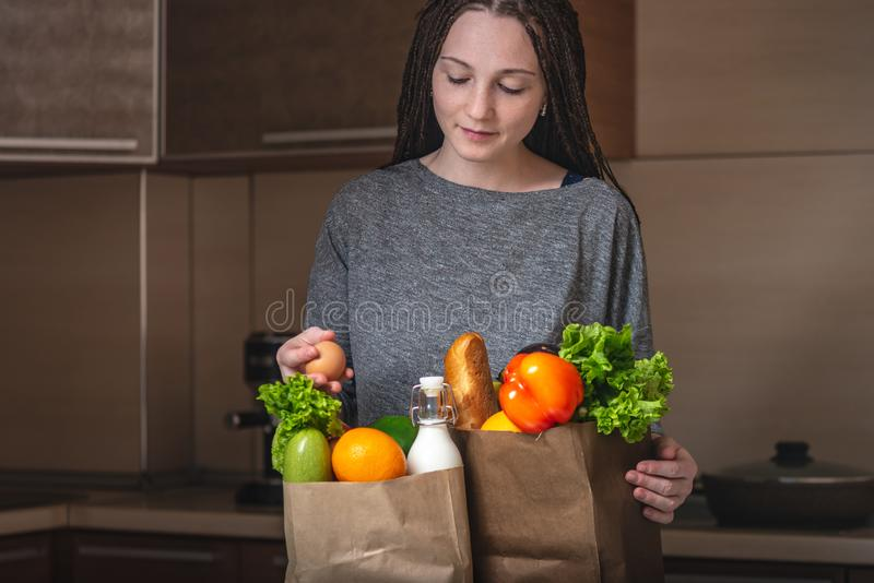 Young woman holding full paper bag with products in hands on the background of the kitchen. Fresh organic food stock image