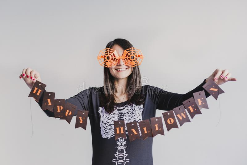 young woman holding a garland with happy halloween sign. White background. LIfestyle indoors. Skeleton costume stock photos