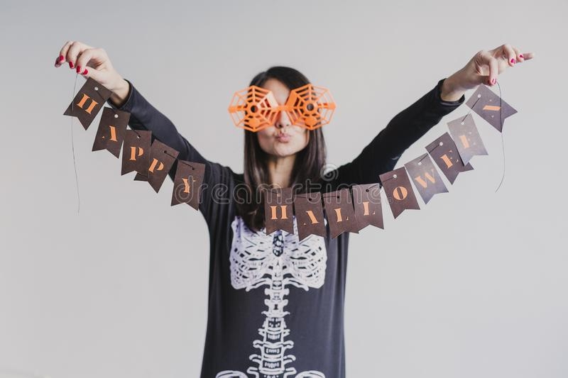 Young woman holding a garland with happy halloween sign. White background. LIfestyle indoors. Skeleton costume. Holiday, pumpkin, fall, face, tradition stock photo