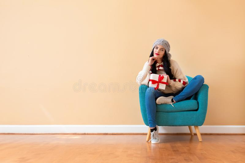 Young woman holding a gift box. Sitting in a chair royalty free stock photo
