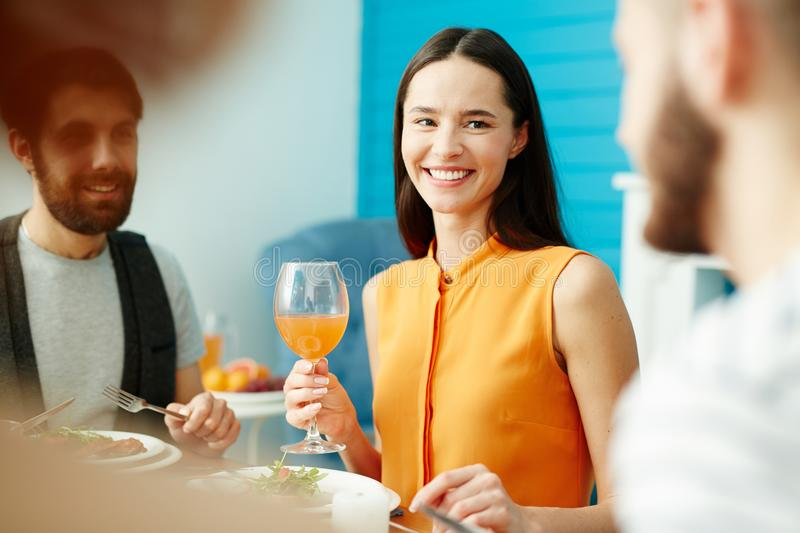 Young woman holding glass while eating with friends stock image