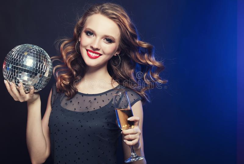 Young woman holding a glass of wine and disco ball at night club royalty free stock photography