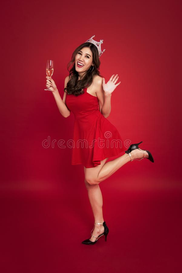 Young woman holding glasses of champagne and smiling while celebrating on red background. christmas and happy new year concept stock photo