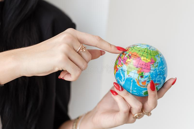 Young woman holding a globe of planet Earth, Showing by finger to Ukraine close-up stock photo