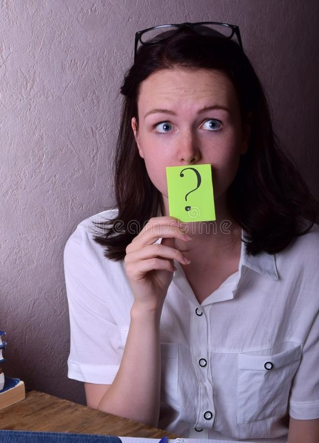 Young woman is holding a green sticker with a question mark stock images