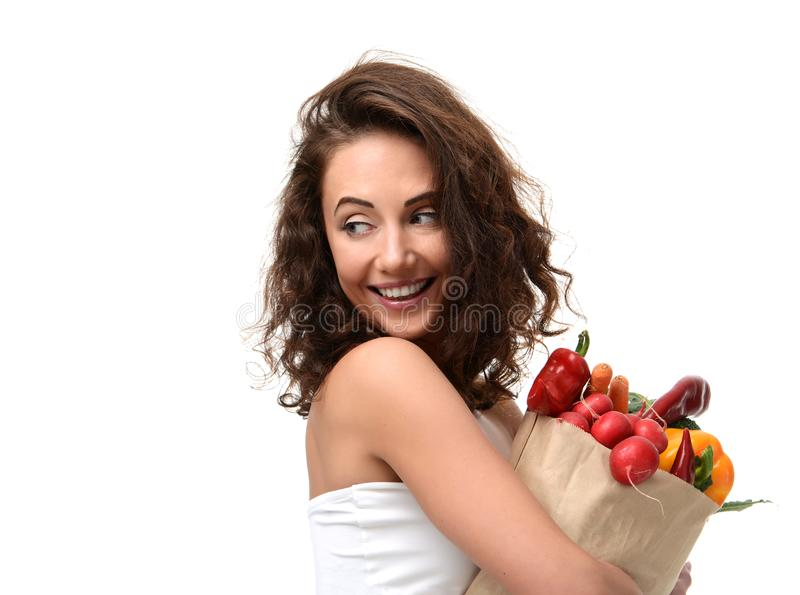 Young woman holding grocery paper shopping bag full of fresh vegetables. Diet healthy eating concept stock image