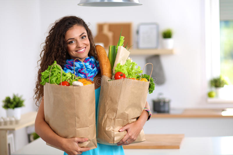 Young woman holding grocery shopping bag with stock image