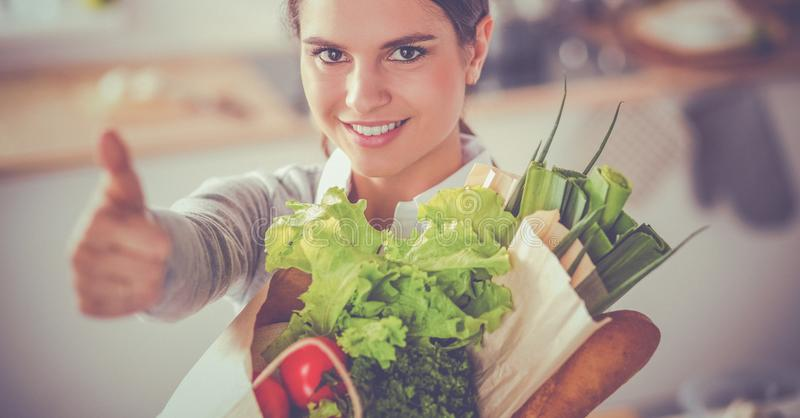 Young woman holding grocery shopping bag with vegetables and showing ok stock photography
