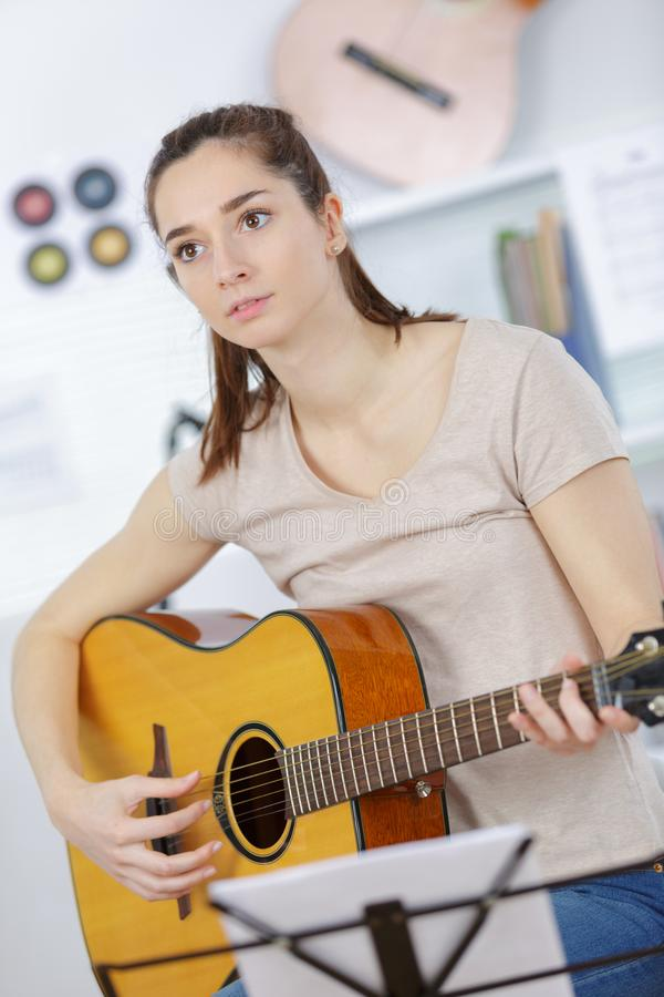 Young woman holding guitar and learning to play song royalty free stock photography