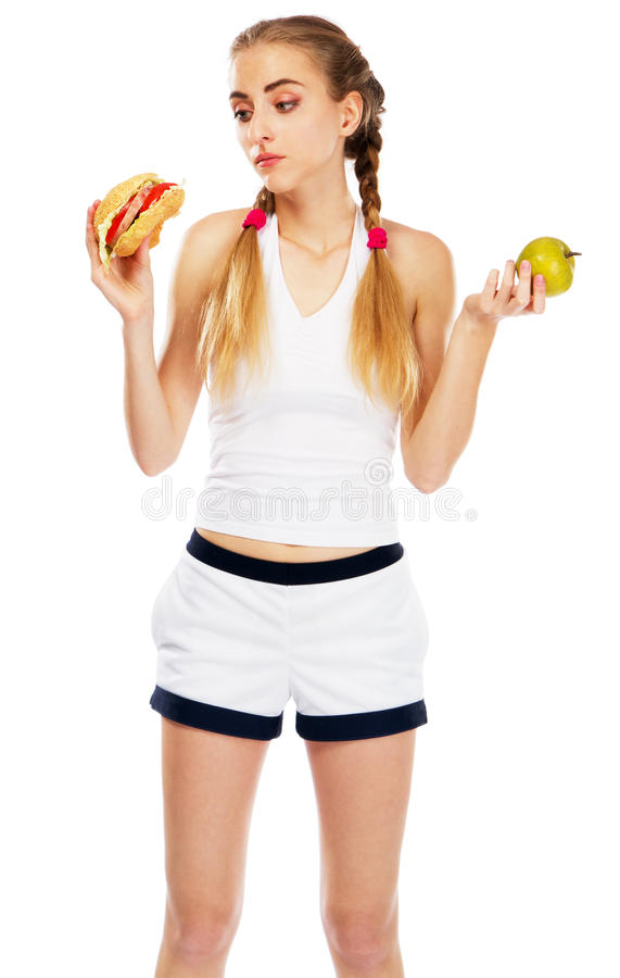 Young woman holding a hamburger and an apple. White background royalty free stock image