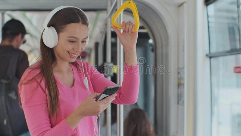 Young woman holding handle while moving in the modern tram. Happy passenger enjoying trip at the public transport. Young woman holding handle while moving in stock photos