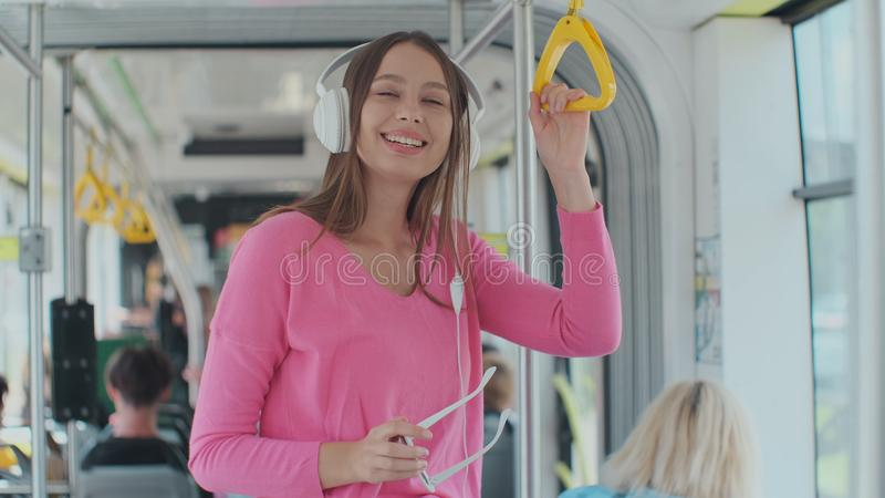 Young woman holding handle while moving in the modern tram. Happy passenger enjoying trip at the public transport. Young woman holding handle while moving in stock images