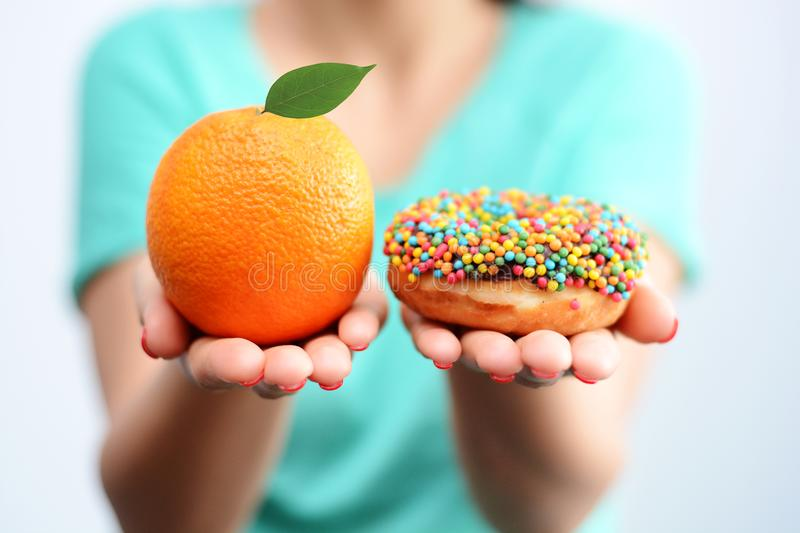 Young woman holding in hands an orange and a tasty multicolored donut, choosing healthy food or dessert stock photo