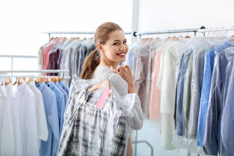 Young woman holding hanger with clothes in plastic bag royalty free stock photos