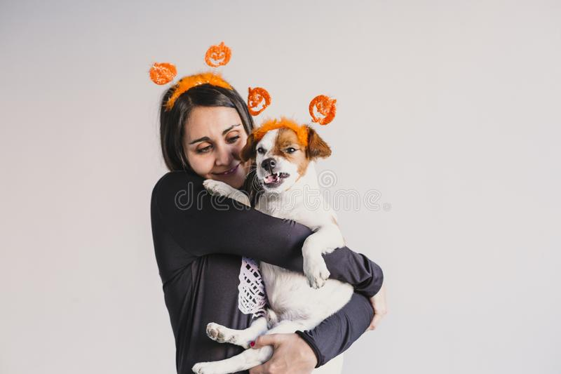 Young woman holding her cute small dog over white background. Matching pumpkin diadems. Halloween concept. Indoors. Holiday, skeleton, mexican, fall, spooky stock image
