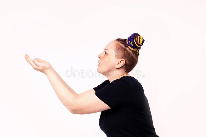 Woman holding her hands together as if catching a ball. The woman has dreadlocks on her head, freckles on her face. On white royalty free stock photo