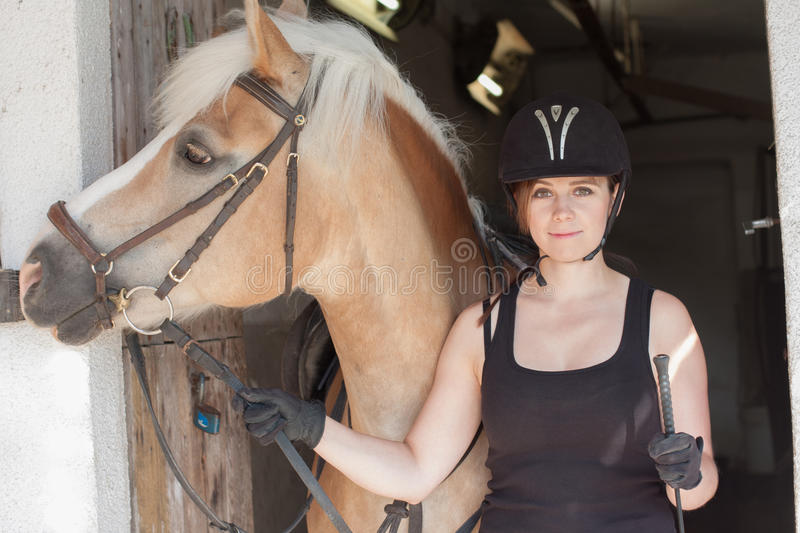 Young woman holding her horse in front of the stable stock photo
