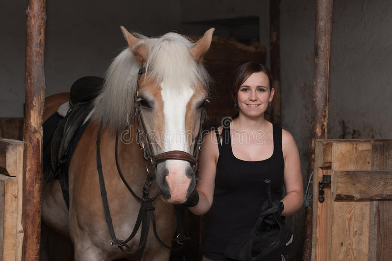 Young woman holding her horse in stable stock photos