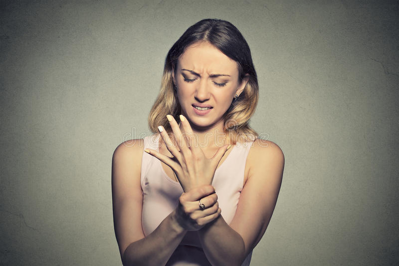 Young woman holding her painful wrist. Sprain pain. Young woman holding her painful wrist isolated on gray wall background. Sprain pain royalty free stock image