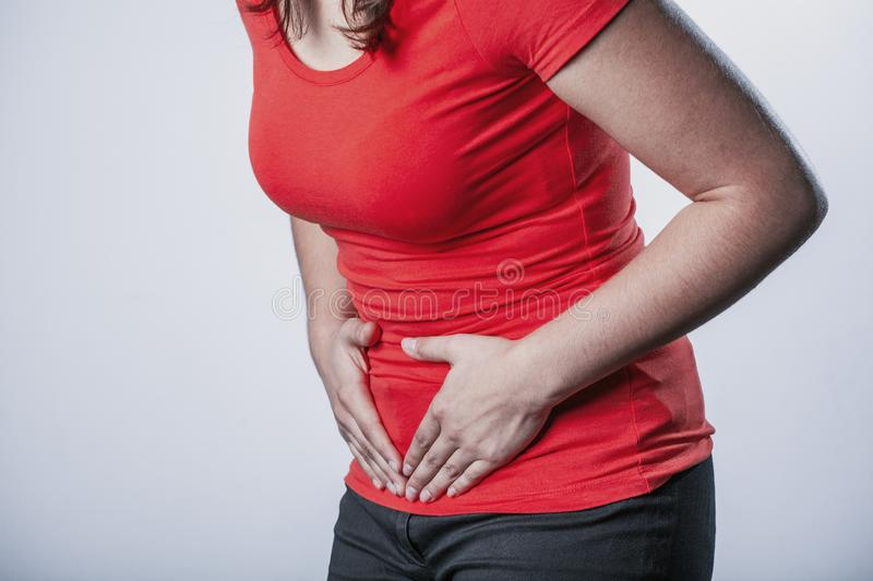 Woman holding her tummy and suffering from menstrual cramps. Young woman holding her tummy and suffering from menstrual cramps stock photo