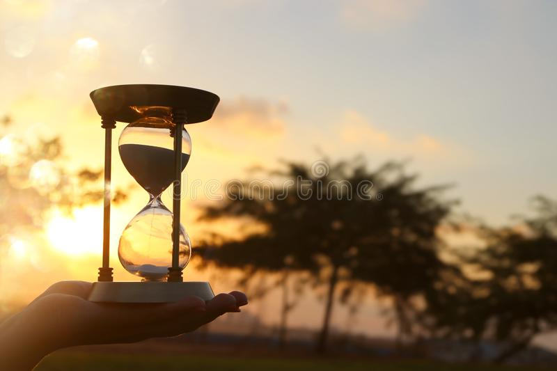Young woman holding Hourglass during sunset. vintage style. royalty free stock image