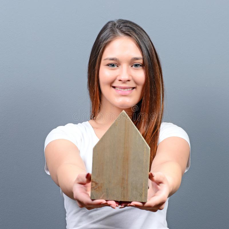 Young woman holding house against gray background -  Real estate concept stock images