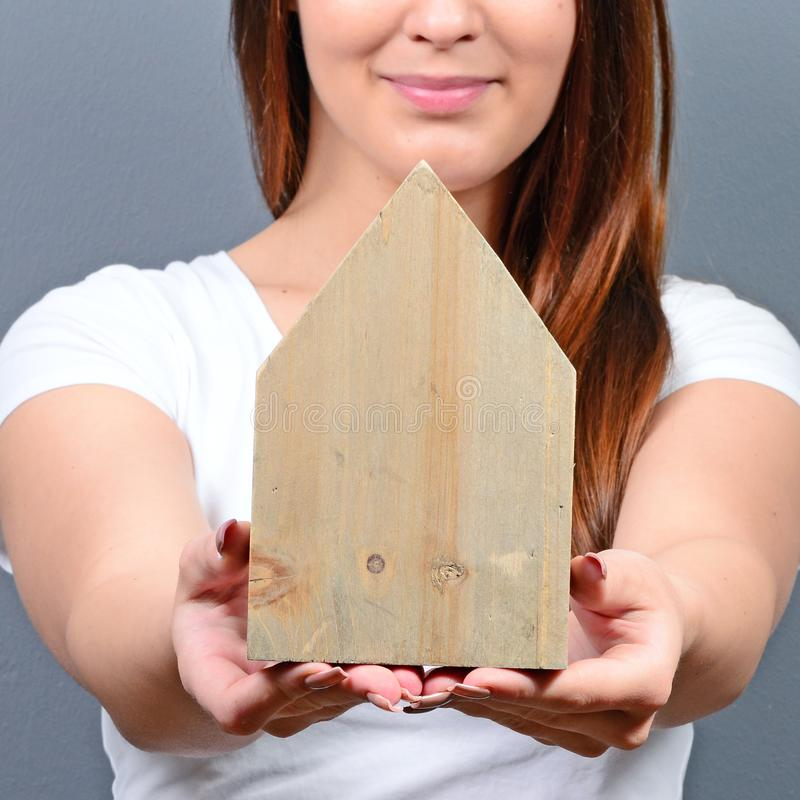 Young woman holding house against gray background -  Real estate concept royalty free stock photography