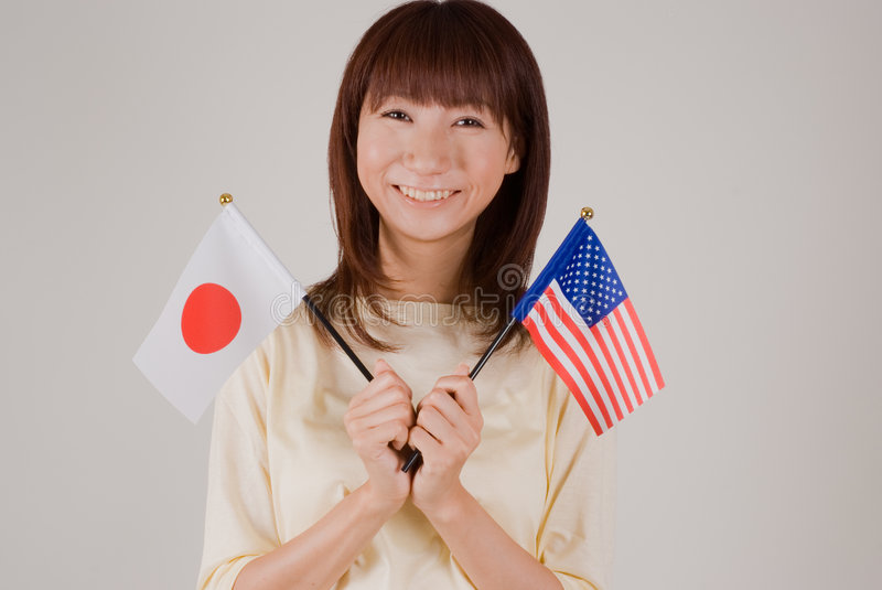 Download Young Woman Holding Japanese And American Flags Royalty Free Stock Photos - Image: 7117058