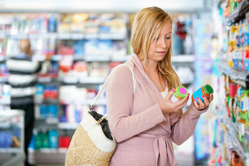 Young woman holding jar in the supermarket royalty free stock images