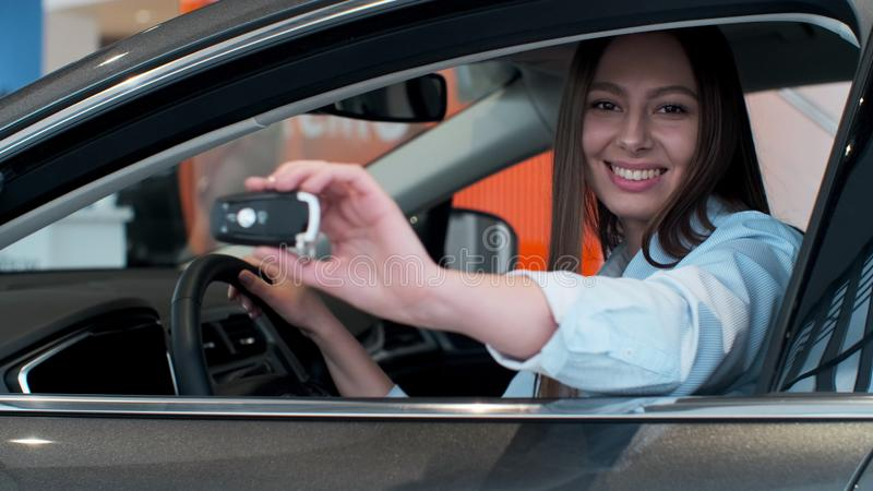 Young woman holding keys to new car auto and smiling at camera. royalty free stock photos