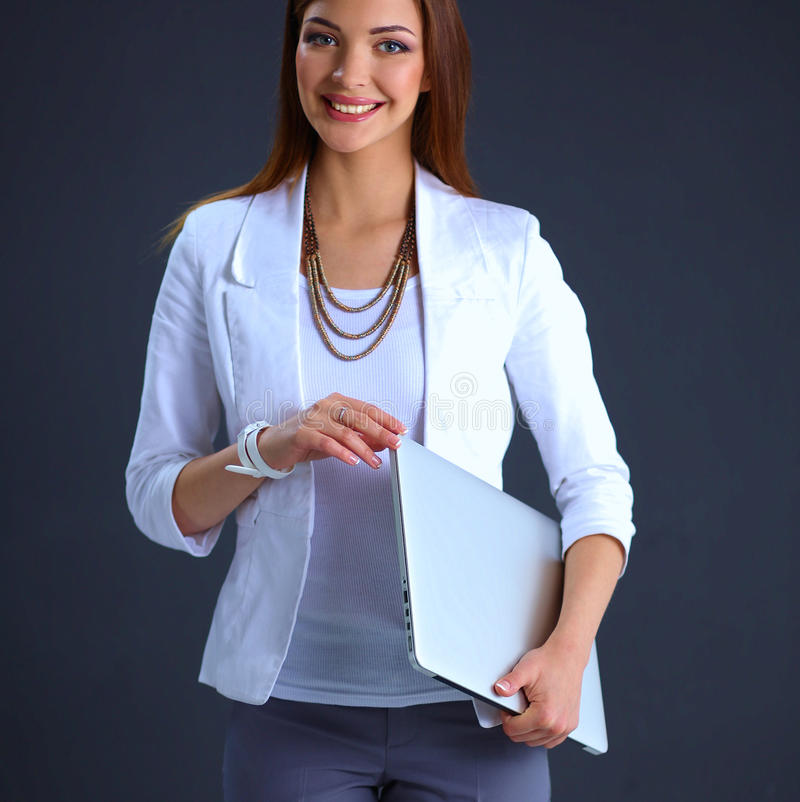 Young woman holding a laptop, isolated on grey background. Portrait of young woman holding a laptop, isolated on grey background stock photography