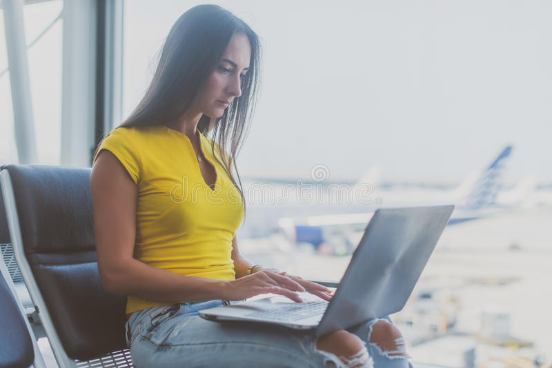 Young woman holding a laptop on lap typing keyboard indoors in airport royalty free stock photos