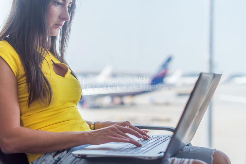 Young woman holding a laptop on lap typing keyboard indoors in airport stock images