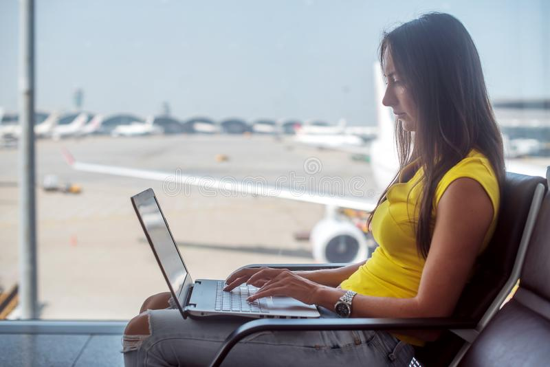 Young woman holding a laptop on lap typing keyboard indoors in airport royalty free stock images