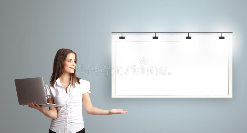 Young woman holding a laptop and presenting modern copy space royalty free stock photography